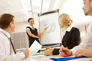 Photo of successful female standing by whiteboard and pointing at diagram on it at seminar