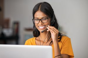 Portrait of cheerful indian woman in smart working from home. Beautiful middle eastern girl working as customer service representative with laptop. Smiling young woman at home with headset doing video call and smiling.