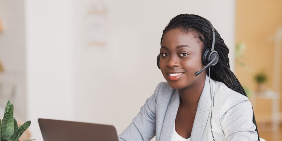Customer support concept. Young afro female manager wearing headset, using laptop at workplace and looking at camera, free space